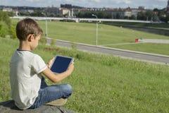 Barn med minnestavlaPC utomhus Pojken på gräs rymmer datoren tillbaka sikt Begrepp för teknologifolkutbildning Arkivbilder