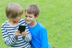 Barn med mobil ringer Två pojkar som ler, ser för att avskärma, spelar lekar eller använder applikation utomhus- teknologi Royaltyfri Bild