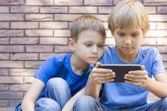 Barn med mobil ringer Två pojkar som ser skärmen, spelar lekar eller använder applikation utomhus- teknologi Arkivfoton