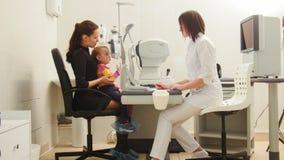 Barn med modern i syncentralen - barnoftalmologi - öga för optometrikerChecks Child ` s royaltyfri fotografi