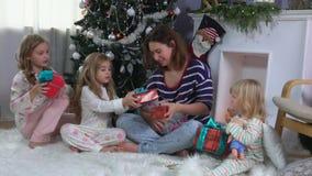 Barn med modern sorterar gåvor under julgranen arkivfilmer