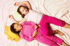 Barn med sömniga framsidor ligger uppemot rosa färgfiltbakgrund fotografering för bildbyråer