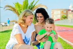 Barn med sammanträde och att skratta för mamma Royaltyfri Bild