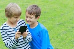 Barn med smartphonen Två pojkar som ser för att avskärma, spelar lekar eller använder applikation utomhus- Teknologiutbildning Arkivbilder