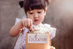 Barn med sparande pengar för utbildningsbegrepp 2 år gammalt barn arkivbilder