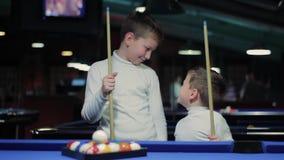 Barn med stickrepliker Pojkar som förbereder sig att spela snooker lager videofilmer
