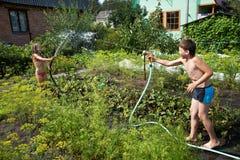 Barn med trädgårds- slangar Royaltyfri Bild