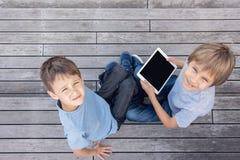 Barn med utomhus- minnestavladatorer Begrepp för fritid folkutbildningsför lärande teknologi Royaltyfria Bilder