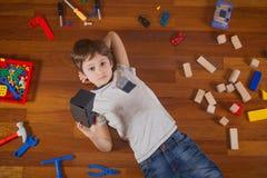 Barn med virtuell verklighet 3D, VR-pappexponeringsglas som ligger på trägolv Många leksaker runt om honom Royaltyfri Foto