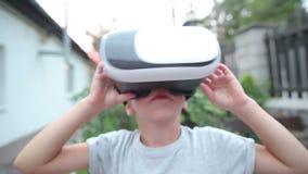 Barn med VR-hörlurar med mikrofon som håller ögonen på, nära övre arkivfilmer