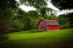 Barn in the Middle of Lawn Surrounded With Trees during Daytime Stock Photography