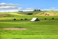 Barn in the middle of rolling hills Stock Photo