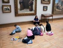 Barn målar sammanträde på golv i det Tretyakov gallerit i Moskva Royaltyfria Bilder