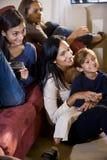 barn mother sittande sofa tre tillsammans Arkivfoto