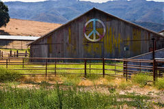 Barn with multicolored peace sign. Multicolored peace sign on side of barn in a rural area Royalty Free Stock Photography