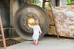 Barn nära den thailändska gongen i Phuket Asiatisk klocka för tradition i buddismtempel i Thailand Berömd stor klockaönska nära g Royaltyfri Fotografi