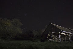 Barn at night with stars. Romanian barn under the night sky with pleiades Stock Photography