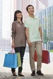 Barn och att le, lyckliga par som utomhus går i Peking med färgrika shoppingpåsar i händer Arkivfoton