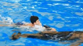 Barn och delfin Den tonåriga pojken simmar med delfin som är hållande på till hans fena arkivfilmer