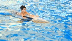 Barn och delfin Den tonåriga pojken simmar med delfin som är hållande på till hans fena stock video