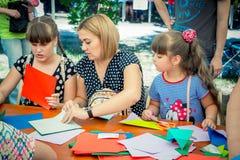 Barn och deras föräldrar som deltar på origamiseminariet arkivbild