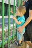 Barn och en vuxen människa på ett staket Royaltyfria Bilder