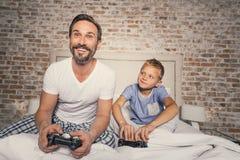 Barn och förälder som tycker om konkurrens Royaltyfria Bilder