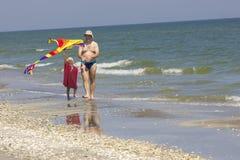 Barn och fader på havssidan Arkivbild