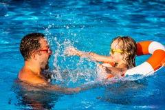 Barn och fader som spelar i simbassäng Royaltyfria Bilder
