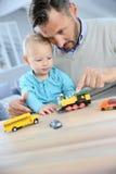 Barn och fader som spelar med leksaker som har gyckel Royaltyfri Fotografi