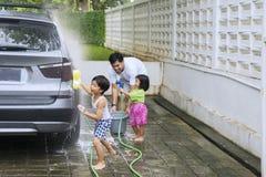 Barn och fader som tvättar en bil arkivfoto