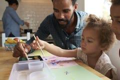 Barn och faderPainting Picture On köksbord fotografering för bildbyråer