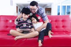 Barn och farsa som använder det smarta huset app på minnestavlan royaltyfri fotografi