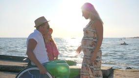 Barn- och farsahållen till mödrar buktar, mannen i rullstol med lilla flickan och gravida kvinnan utomhus arkivfilmer