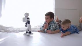 Barn och framtid, moderna ungar som ligger på golv, och vinkande händer till den humanoid roboten som går till dem stock video