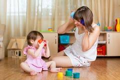 Barn och hennes moder som spelar samman med leksaker Arkivfoto