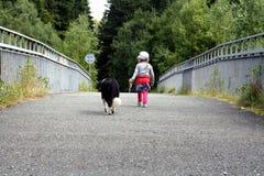 Barn och hund för en gå Arkivfoton