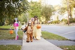 Barn och hund i allhelgonaaftondräkter för trick eller behandling royaltyfri fotografi