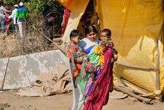 Barn och kvinna som rymmer dem på bygatan Arkivfoto