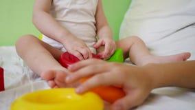 Barn- och mammalek med mång--färgade kuber och cirklar på säng Bildande leksaker för förtränings- och dagisbarn stock video