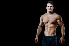 Barn och manlig modell för passform som poserar hans muskler Arkivbild