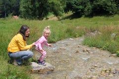 Barn och moder på floden Royaltyfri Foto