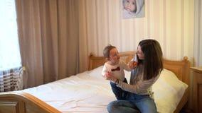 Barn och moder p? s?ng Mamman och behandla som ett barn pojken som spelar i soligt sovrum F?r?lder och liten unge som hemma koppl stock video