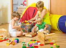 Barn och moder som samlar leksaker Arkivfoto