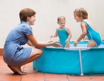 Barn och moder som spelar i pöl Arkivfoton