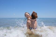 Barn och moder som spelar med vågor i strand Arkivfoto