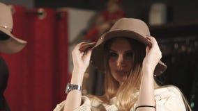 Barn och nätt kvinna som försöker på en hatt med fält i en moderiktig boutique arkivfilmer