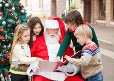 Barn och Santa Claus Reading Book Arkivfoto