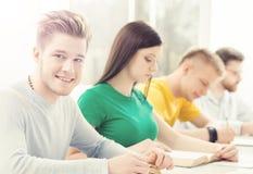 Barn och smarta studenter som lär i ett klassrum Royaltyfri Bild