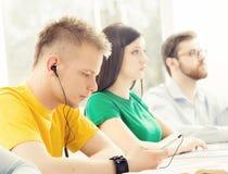 Barn och smarta studenter som lär i ett klassrum Arkivbild